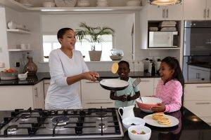 Mother And Children Preparing Food On A Worktop In Kitchen At Home