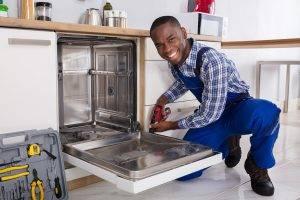 Repairman Installing Dishwasher In Kitchen